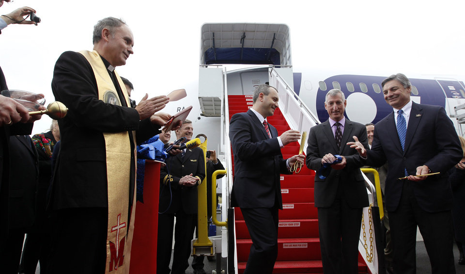 Photo -   Fr. Stanislaw Michalek, left, looks on as LOT Polish Airlines executive Tomasz Balcerzak, center, shakes hands with Boeing executives Ray Conner, right, and Larry Loftis in front of a Boeing 787 during a delivery ceremony Wednesday, Nov. 14, 2012, at Paine Field in Everett, Wash. LOT Polish Airlines took delivery of its first Boeing 787 and plans to fly early next year on routes between Poland and New York, Chicago and Toronto. Poland's LOT was Europe's first airline to purchase the new plane with an order for eight. Boeing says the 787 is the first mid-size plane capable of flying long-range routes, allowing airlines to open new, non-stop flights. (AP Photo/Elaine Thompson)