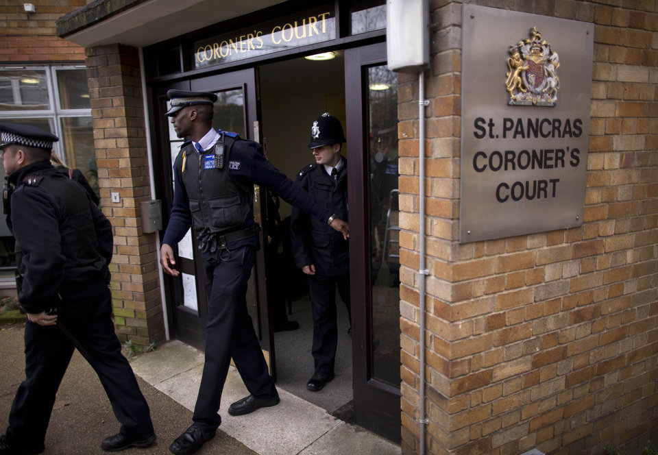 Photo - Police officers and a community support officer, center, leave after a second inquest into the death of singer Amy Winehouse at St. Pancras Coroner's Court in London, Tuesday, Jan. 8, 2013. A second coroner's inquest confirmed Tuesday, that Amy Winehouse died of accidental alcohol poisoning when she resumed drinking after a period of abstinence. The second inquest was held after the original coroner was found to lack the proper qualifications for the job.  (AP Photo/Matt Dunham)