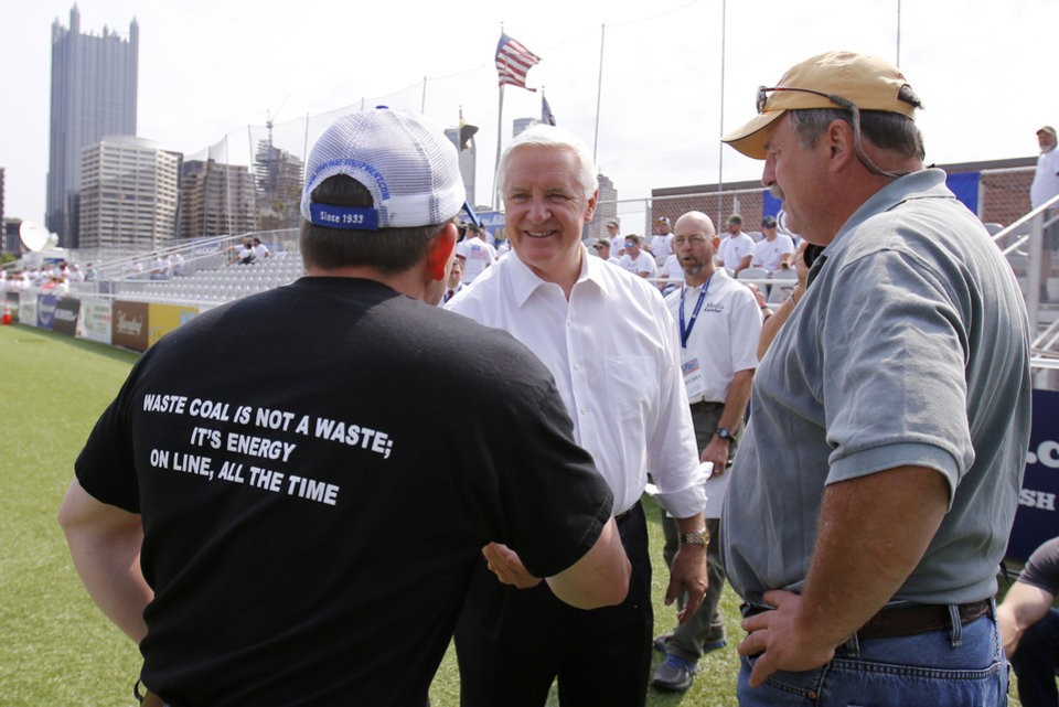 Photo - Pennsylvania Governor Tom Corbett, center, visits with attendees at a rally to support American energy and jobs in the coal and related industries at Highmark Stadium in downtown Pittsburgh, Wednesday, July 30, 2014. The rally is being held the day before the Environmental Protection Agency conducts public hearings on its new emissions regulations for existing coal fired power plants. (AP Photo/Gene J. Puskar)