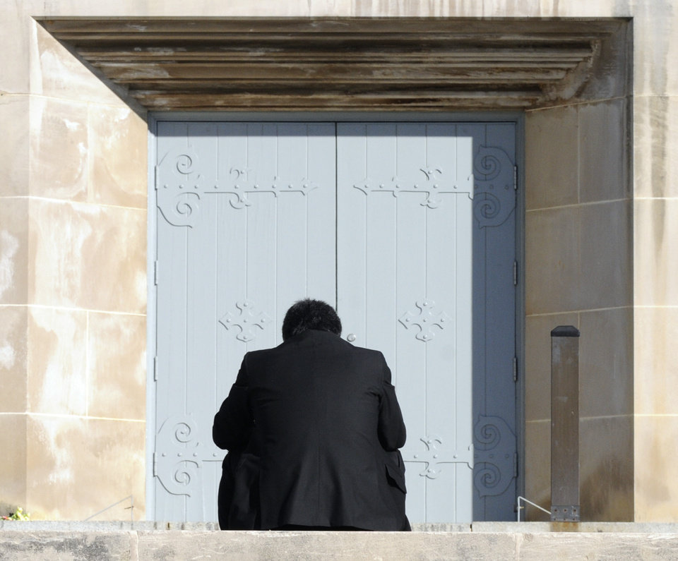 Photo -   FILE - In this April 15, 2008 file photo, a mourner sits on a wall in front of the entrance to Norris Hall prior to a memorial ceremony for the victims of the April 16, 2007 shootings on the campus of Virginia Tech in Blacksburg, Va. Each anniversary since the April 2007, massacre on the Virginia Tech campus, classes have been suspended for the day in memory of the 32 students and faculty killed in the rampage by a lone gunman who then killed himself. On Monday, April 16, 2012, the fifth anniversary of the deadliest mass shooting in modern U.S. history, the 28,000 students on campus will head to class to honor the 32. (AP Photo/Don Petersen, File)