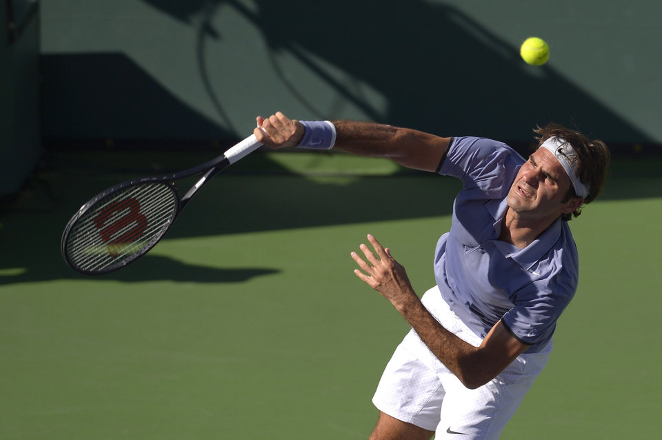 Photo - Roger Federer, of Switzerland, hits to Novak Djokovic, of Serbia, in the final match of the BNP Paribas Open tennis tournament, Sunday, March 16, 2014, in Indian Wells, Calif. (AP Photo/Mark J. Terrill)