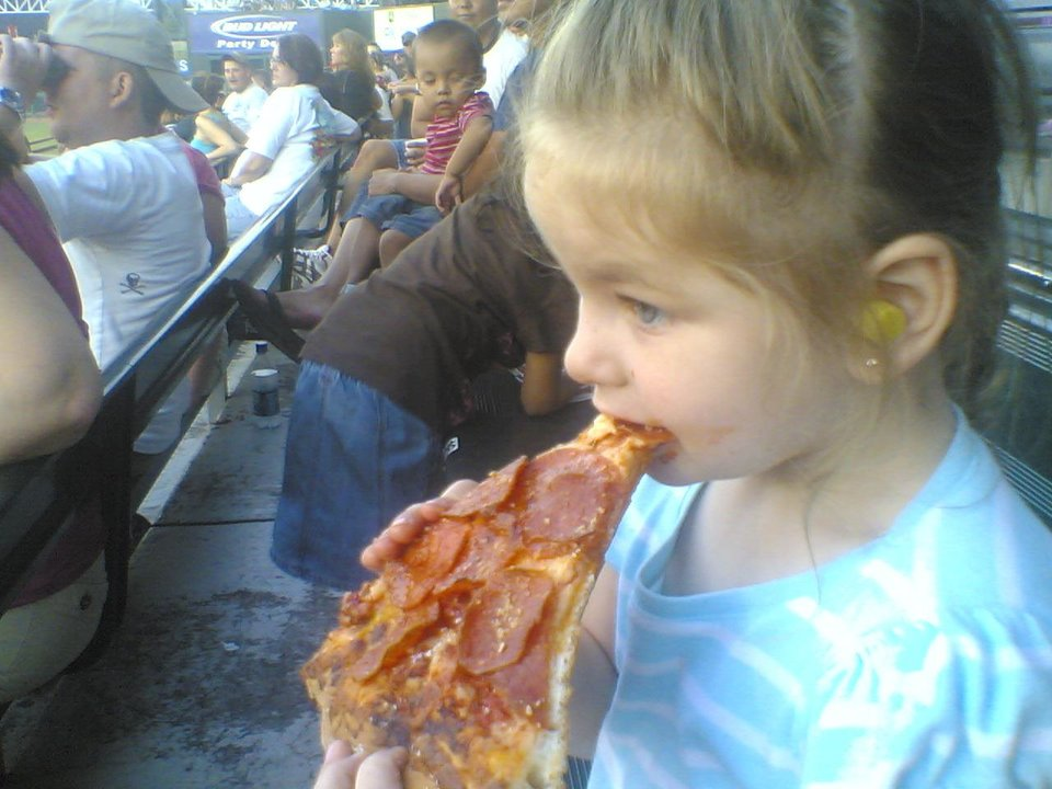 Lauren Goodman enjoys a slice of pizza while watching the last home game for the 2007 Redhawks season. Community Photo By: Darryl Goodman Submitted By: Darryl, Warr Acres