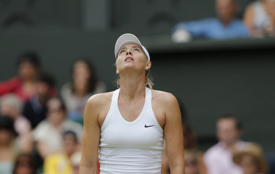 Photo - Maria Sharapova of Russia looks dejected after losing a point to Angelique Kerber of Germany during their women's singles match at the All England Lawn Tennis Championships in Wimbledon, London, Tuesday, July 1, 2014. (AP Photo/Ben Curtis)