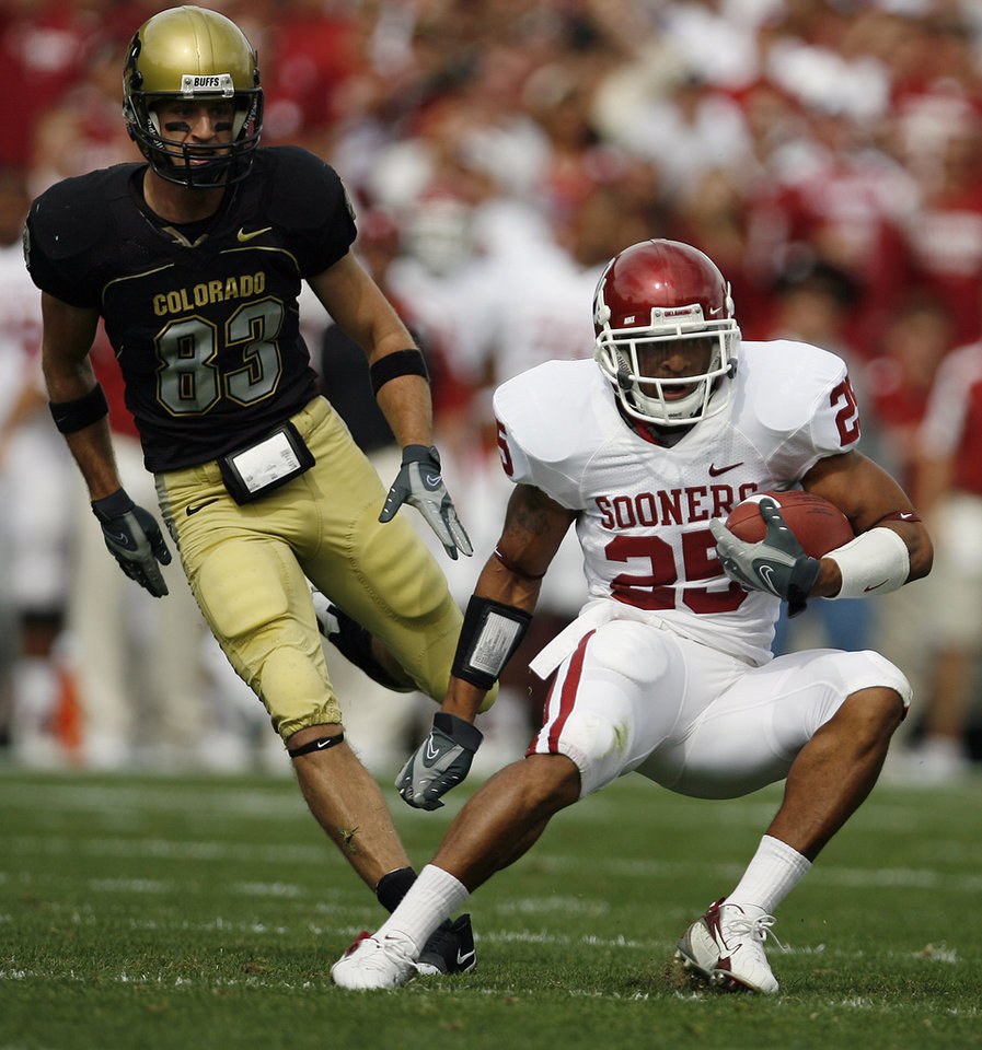 Photo - Oklahoma's D.J. Wolfe (25) returns a interception in front of Colorado's Dusty Sprague (83) during the first half of the college football game between the University of Oklahoma Sooners (OU) and the University of Colorado Buffaloes (CU) at Folsom Field on Saturday, Sept. 28, 2007, in Boulder, Co.  By Bryan Terry, The Oklahoman