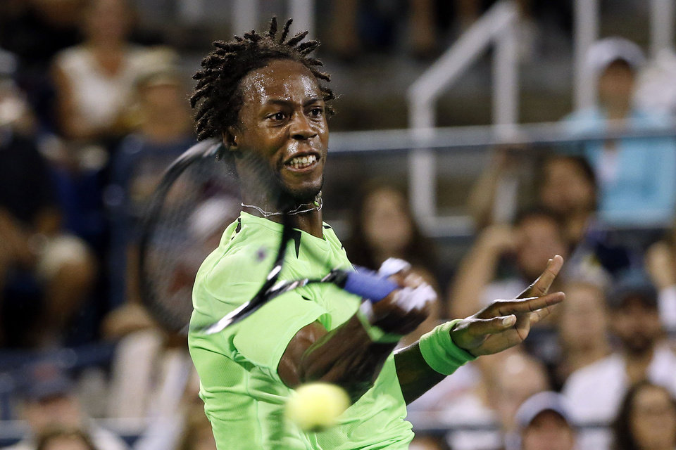 Photo - Gael Monfils, of France, returns a shot to Richard Gasquet, of France, during the third round of the U.S. Open tennis tournament Sunday, Aug. 31, 2014, in New York. (AP Photo/Jason DeCrow)
