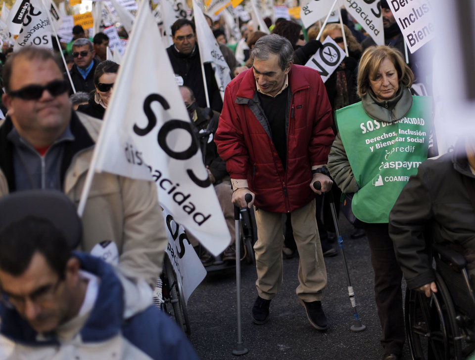 Photo - A man walks assisted by crutches, as people march and display banners reading,