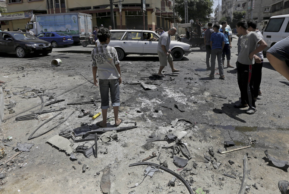 Photo - Palestinians search the site of the wreckage of a vehicle following an Israeli airstrike at the main street in Gaza City in the northern Gaza Strip, Thursday, Aug. 21, 2014. At least two were killed in the car outside a grocery shop, and a few others were wounded by an Israel airstrike on a Gaza City street, according to the Palestine Red Crescent Society. (AP Photo/Adel Hana)