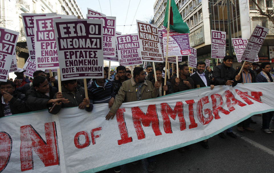 Photo -   FILE - In this March 17 2012, file photo, immigrants holding placards that read
