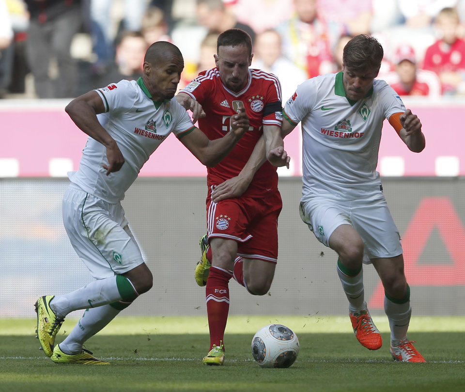 Photo - Bayern's Franck Ribery of France, center, Bremen's Theodor Gebre Selassie of Czech Republic, left, and Bremen's Clemens Fritz challenge for the ball during the German first division Bundesliga soccer match between FC Bayern Munich and SV Werder Bremen in Munich, southern Germany, Saturday, April 26, 2014. (AP Photo/Matthias Schrader)