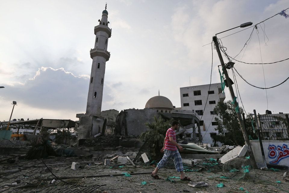 Photo - A Palestinian man walks past the Al Aqsa Martyrs mosque, destroyed by an overnight Israeli strike, in Gaza City, Tuesday, July 22, 2014. Israel bombed five mosques, a sports stadium and the home of the late Hamas military chief across the Gaza Strip early on Tuesday, a Gaza police official said, as the U.N. chief Ban Ki-moon and the U.S. Secretary of State John Kerry launched a high-level effort to end two weeks of deadly fighting. (AP Photo/Lefteris Pitarakis)