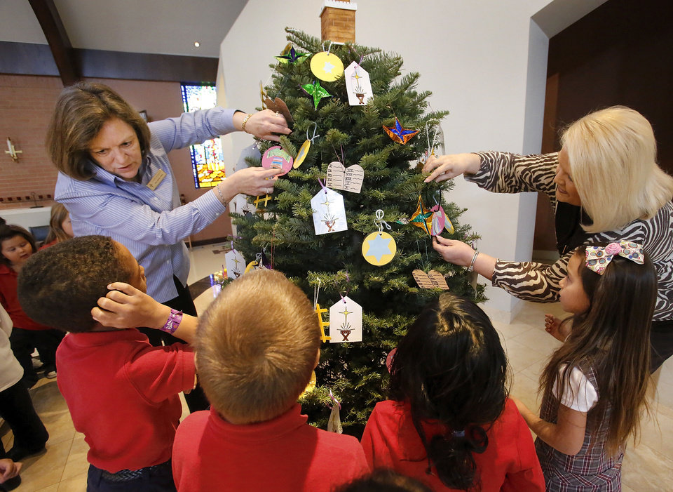 St. James Catholic School teacher Brenda Tener, left, and the school's principal, Anne Codding, right, help students hang their ornaments on the Jesse tree placed near the altar at St. James the Greater Catholic Church in south Oklahoma City. Photos by Jim Beckel, THE OKLAHOMAN