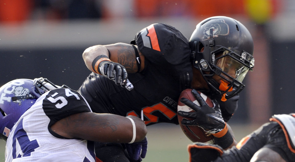 Photo -   Oklahoma State receiver Josh Stewart, right, is tackled by TCU linebacker Marcus Mallet after gaining 16 yards during the second half of an NCAA college football game in Stillwater, Okla., Saturday, Oct. 27, 2012. Stewart had six catches for 120 yards in the 36-14 Oklahoma State win. (AP Photo/Brody Schmidt)
