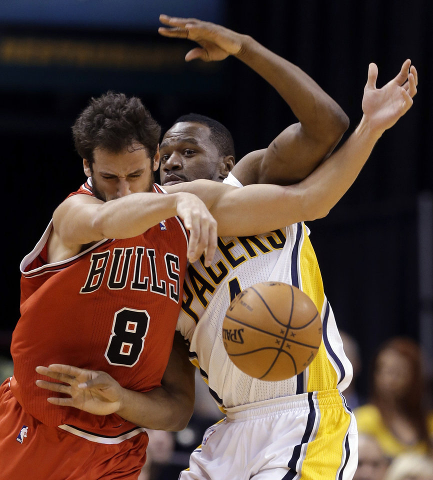 Photo - Chicago Bulls guard Marco Belinelli, left, and Indiana Pacers forward Sam Young get tied up in the second half of an NBA basketball game in Indianapolis, Monday, Feb. 4, 2013. The Pacers defeated the Bulls 111-101. (AP Photo/Michael Conroy)