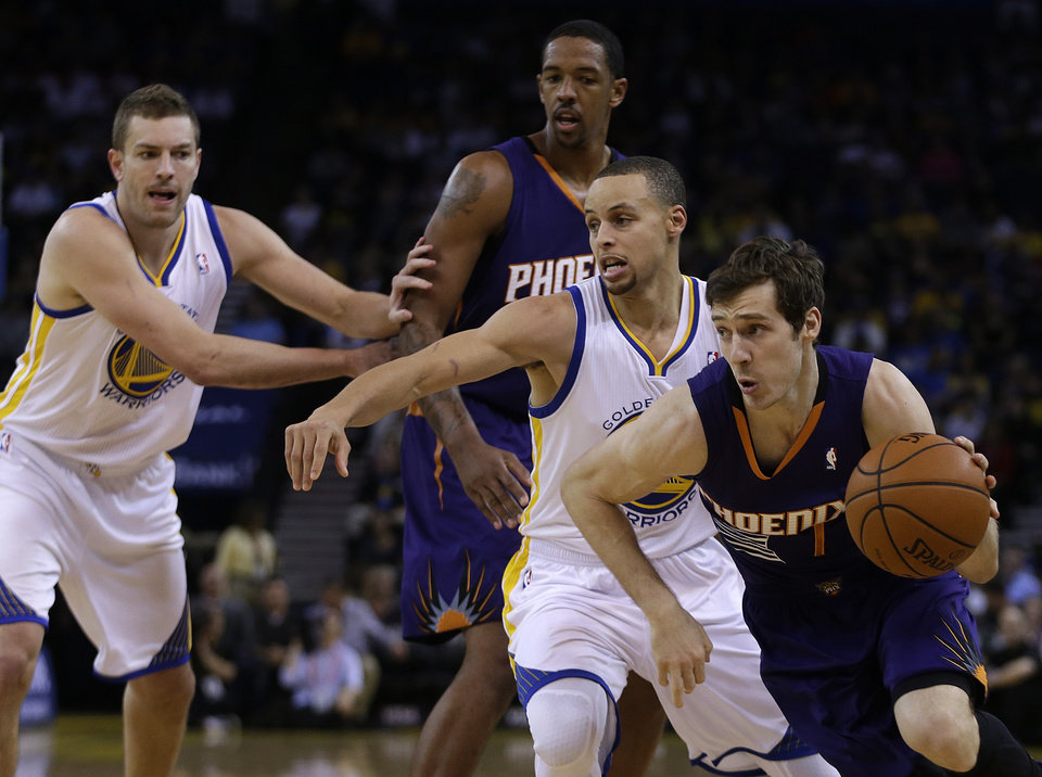 Photo - Phoenix Suns' Goran Dragic, right, drives past Golden State Warriors' Stephen Curry, second from right, during the first half of an NBA basketball game Sunday, March 9, 2014, in Oakland, Calif. (AP Photo/Ben Margot)