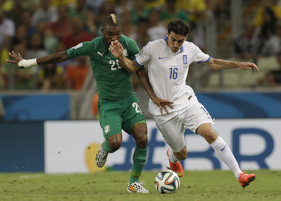 Photo - Ivory Coast's Serey Die, left, and Greece's Lazaros Christodoulopoulos challenge for the ball during the group C World Cup soccer match between Greece and Ivory Coast at the Arena Castelao in Fortaleza, Brazil, Tuesday, June 24, 2014. (AP Photo/Natacha Pisarenko)