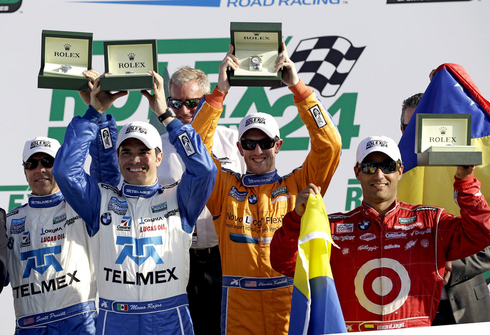 Photo - ADDS FIVE-TIME ROLEX CHAMPION HURLEY HAYWOOD -From left, Ganassi Racing team drivers Scott Pruett, Memo Rojas, of Mexico, Charlie Kimball and Juan Pablo Montoya, of Colombia, hold up their Rolex watches given to them for winning the Grand-Am Series Rolex 24 hour auto race at Daytona International Speedway, Sunday, Jan. 27, 2013, in Daytona Beach, Fla. Five-time Rolex champion Hurley Haywood, background center, looks on. (AP Photo/John Raoux)