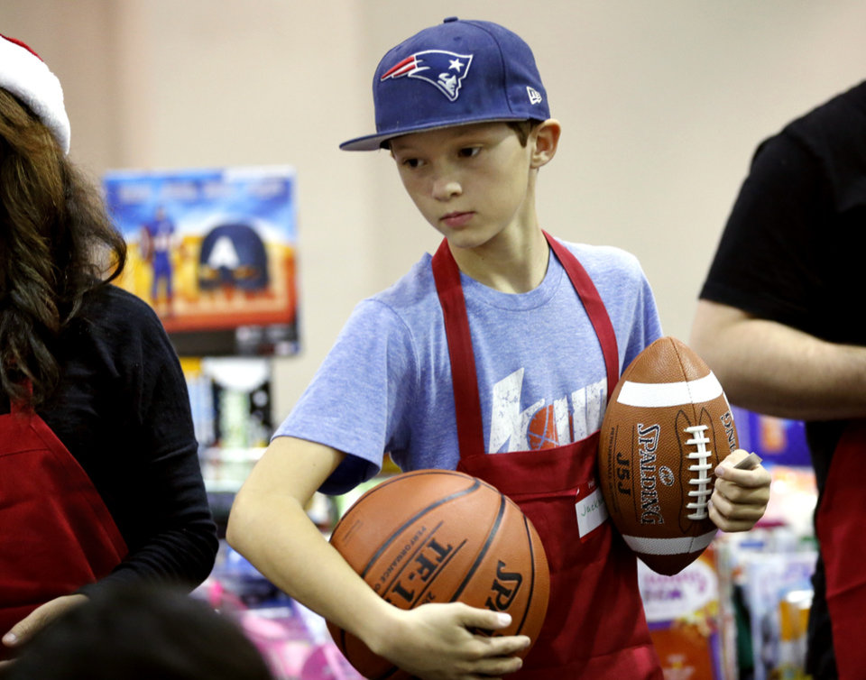 Photo -  Jackson Cassil, 12, passes out presents. [Photo by Steve Sisney, The Oklahoman]