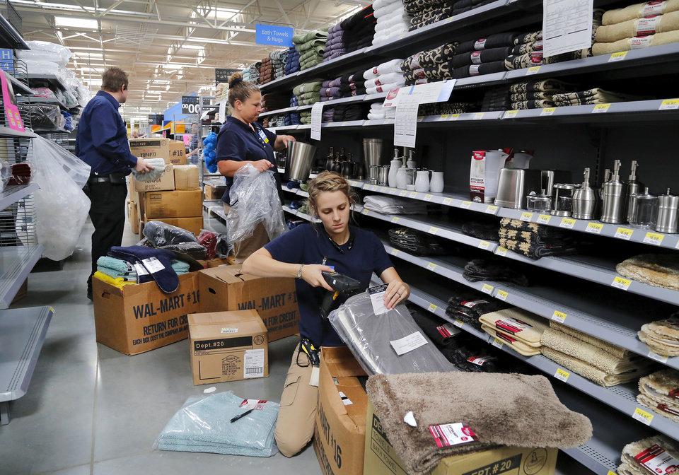 Photo -  Samantha Bland, front, and Bonnie VanderGeeten, center, unpack merchandise and stock shelves in the bath section as workers prepare for the opening of Choctaw's first Walmart in July. At left is Gene Simmons, store co-manager. Photo by Jim Beckel, The Oklahoman   Jim Beckel -