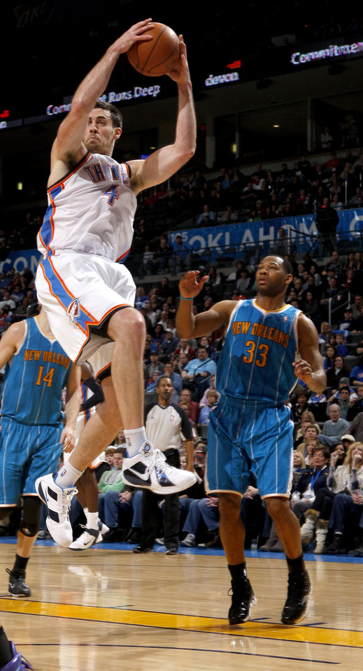 Photo - Oklahoma City's Nick Collison (4) grabs a rebound over New Orleans' Willie Green (33) during the NBA basketball game between the Oklahoma City Thunder and the New Orleans Hornets, Wednesday, Feb. 2, 2011 at the Oklahoma City Arena. Photo by Bryan Terry, The Oklahoman