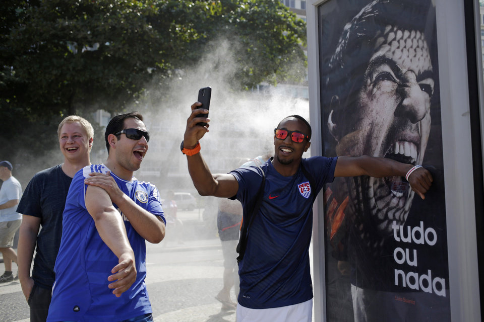 Photo - A U.S. soccer fan pretends that Uruguay's soccer striker Luis Suarez is biting him as he takes a selfie next to an Adidas advertisement featuring Suarez near Copacabana beach in Rio de Janeiro, Brazil, Thursday, June 26, 2014. FIFA banned Suarez from all football activities for four months on Thursday for biting an opponent at the World Cup, a punishment that rules him out of the rest of the tournament. (AP Photo/Matt Dunham)