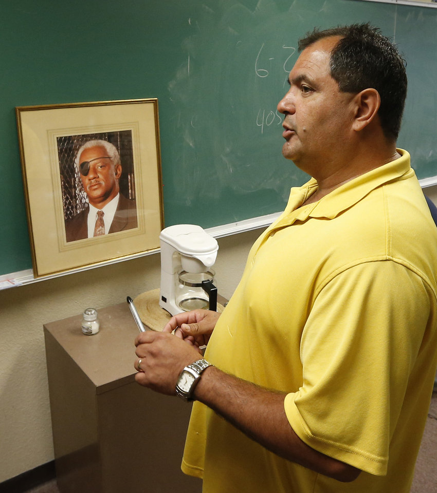 Aaron Cosar speaks in his classroom at The Education and Employment Ministry (TEEM), where Cosar works as a life-skills instructor, in Oklahoma City, Monday, June 24, 2013. Former Oklahoma Gov. Brad Henry commuted the life sentence of Cosar and signed his parole, while he was governor. The framed photograph is of the late former prison warden Ray Little, who Cosar describes as a mentor. (AP Photo/Sue Ogrocki)