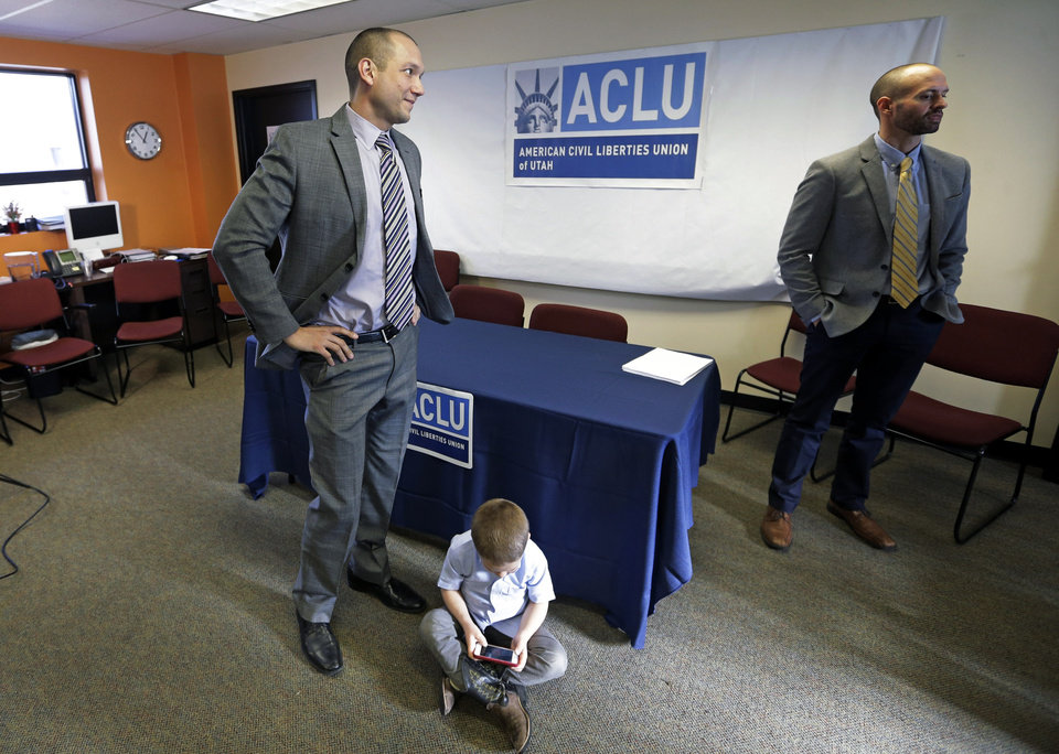 Photo - Plaintiffs Matthew Barraza, left, and his husband Tony Milner, right, look on as their son Jesse, 4, plays, following a news conference on Tuesday, Jan. 21, 2014, in Salt Lake City. The American Civil Liberties Union has sued the state of Utah over the issue of gay marriage, saying the official decision to stop granting benefits for newly married same-sex couples has created wrenching uncertainty. The lawsuit filed Tuesday says the state has put hundreds of gay and lesbian couples in legal limbo and prevented them from getting key protections for themselves and their children. (AP Photo/Rick Bowmer)