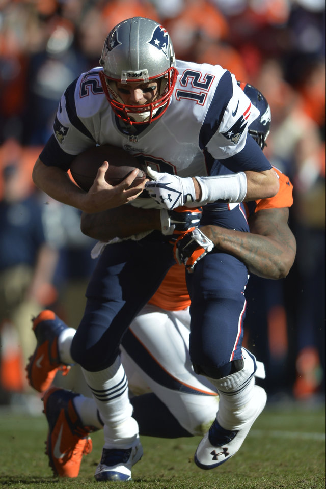 Photo - New England Patriots quarterback Tom Brady (12) is sacked by Denver Broncos defensive end Robert Ayers (91) during the first half of the AFC Championship NFL playoff football game in Denver, Sunday, Jan. 19, 2014. (AP Photo/Jack Dempsey)