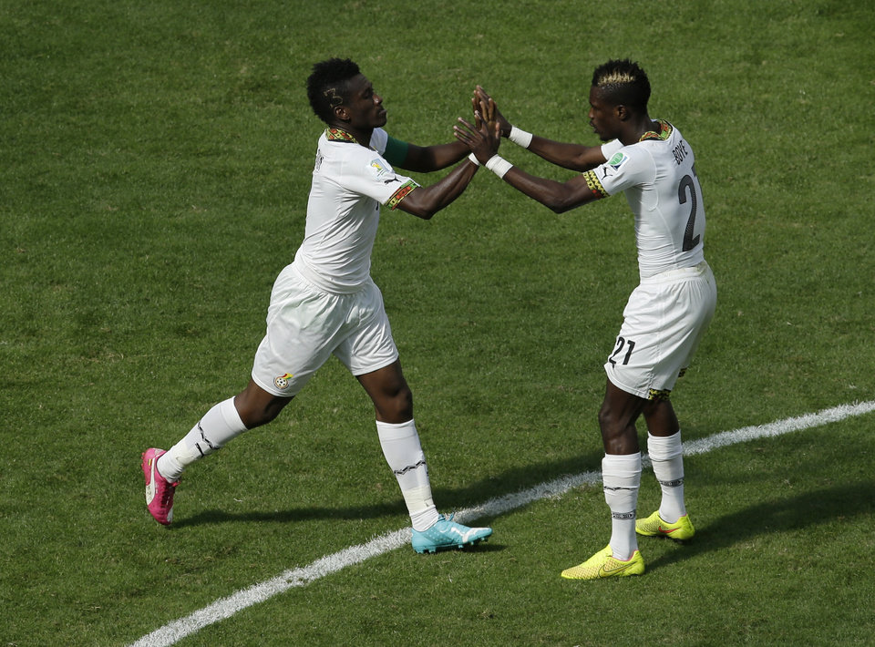 Photo - Ghana's Asamoah Gyan, left, celebrates with Ghana's John Boye, right, after Gyan scored his side's first goal during the group G World Cup soccer match between Portugal and Ghana at the Estadio Nacional in Brasilia, Brazil, Thursday, June 26, 2014. (AP Photo/Themba Hadebe)