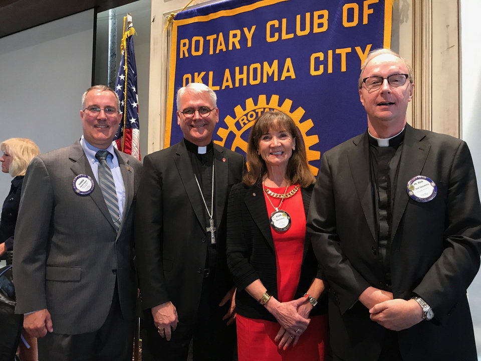 Photo - Patrock Raglow, Archbishop Paul S. Coakley, Ellen Fleming and the Rev. Rick Stansberry pose for a photo on Tuesday, Sept. 5, at the Rotary Club of Oklahoma City's luncheon at the Petroleum Club. [Photo by Carla Hinton, The Oklahoman]