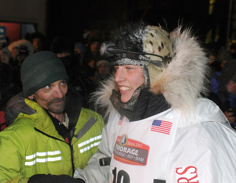 Photo - Four time Iditarod champion Lance Mackey, left, greets Aliy Zirkle after Zirkle finished in second place behind race winner Dallas Seavey in the 2014 Iditarod Trail Sled Dog Race in Nome, Alaska, Tuesday, March 11, 2014. (AP Photo/The Anchorage Daily News, Bob Hallinen)  LOCAL TV OUT (KTUU-TV, KTVA-TV) LOCAL PRINT OUT (THE ANCHORAGE PRESS, THE ALASKA DISPATCH)