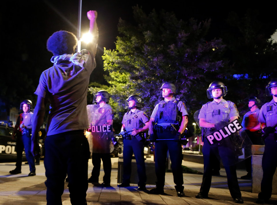 Photo - A protestor raises their arm in front of the Oklahoma City police line at the police station in Oklahoma City, Saturday, May 30, 2020. The protest was in response to the death of George Floyd. [Sarah Phipps/The Oklahoman]