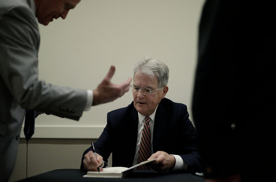 Photo - Daniel Ketchum(left) speaks with former Senator Dr. Tom Coburn as he signs a book that Ketchum purchesed at the Rotary Club of Tulsa April 25, 2018.  MIKE SIMONS/Tulsa World