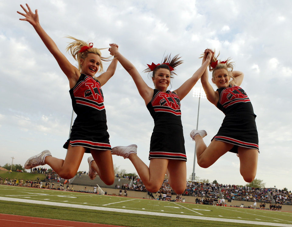 Photo - Westmoore cheerleaders Madison Auge, Tristen Cook and Karley Brock leap for a school photographer before the game as the Jaguars play the Southmoore Sabercats in high school football on Friday, Sept. 7, 2012, in Moore, Okla.  Photo by Steve Sisney, The Oklahoman