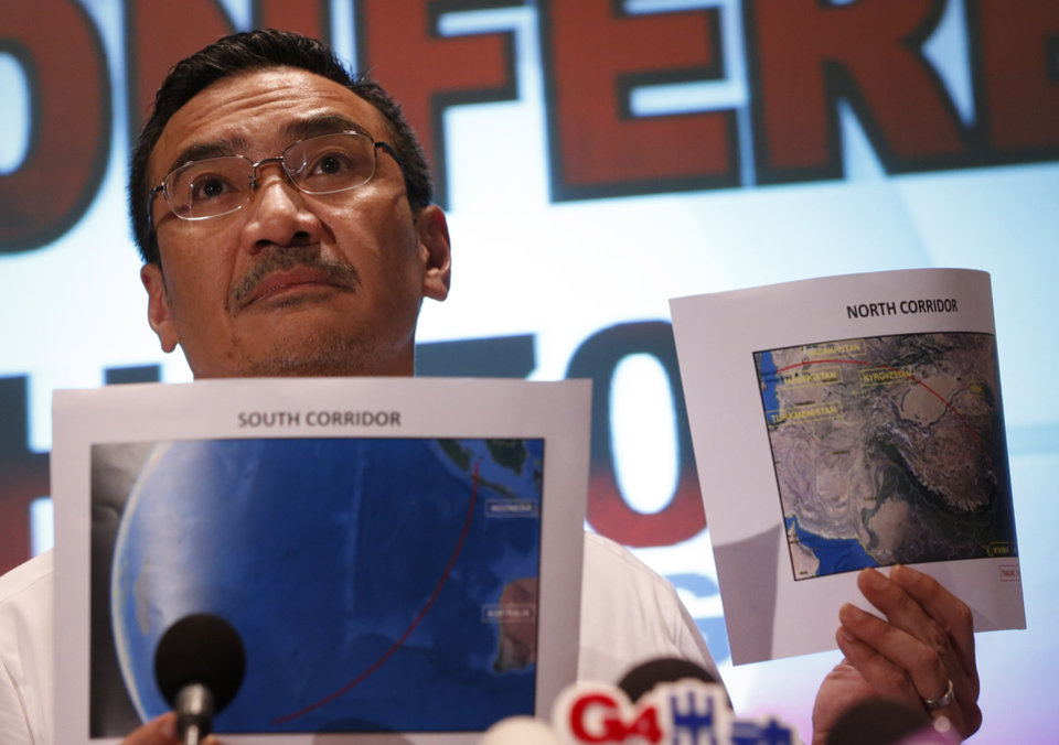 Photo - Malaysia's acting Transport Minister Hishamuddin Hussein shows maps of southern corridor and northern corridor of the search and rescue operation during a press conference at a hotel near the Kuala Lumpur International Airport, in Sepang, Malaysia, Monday, March 17, 2014. Twenty-six countries are involved in the massive international search for the Malaysia Airlines jetliner that disappeared on March 8 with 239 people aboard. They include not just military assets on land, at sea and in the air, but also investigators and the specific support and assistance requested by Malaysia, such as radar and satellite information. (AP Photo/Vincent Thian)