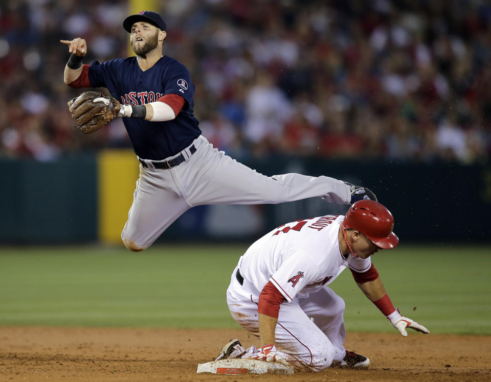 Photo - Boston Red Sox's Dustin Pedroia, top, throws to first base to complete a double play after forcing out Los Angeles Angels' Mike Trout, bottom, during the third inning of a baseball game in Anaheim, Calif., Friday, July 5, 2013. Angels' Albert Pujols was out at first. (AP Photo/Jae C. Hong)