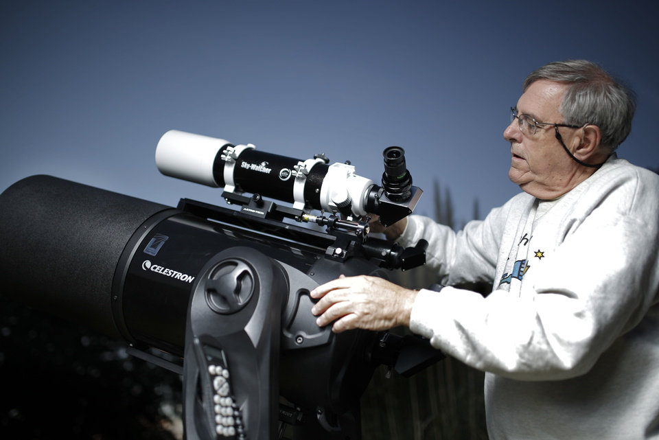 Photo - Mike Brake adjusts his telescope at his home, Tuesday, Oct. 8, 2013, in Oklahoma City. Photo by Sarah Phipps, The Oklahoman
