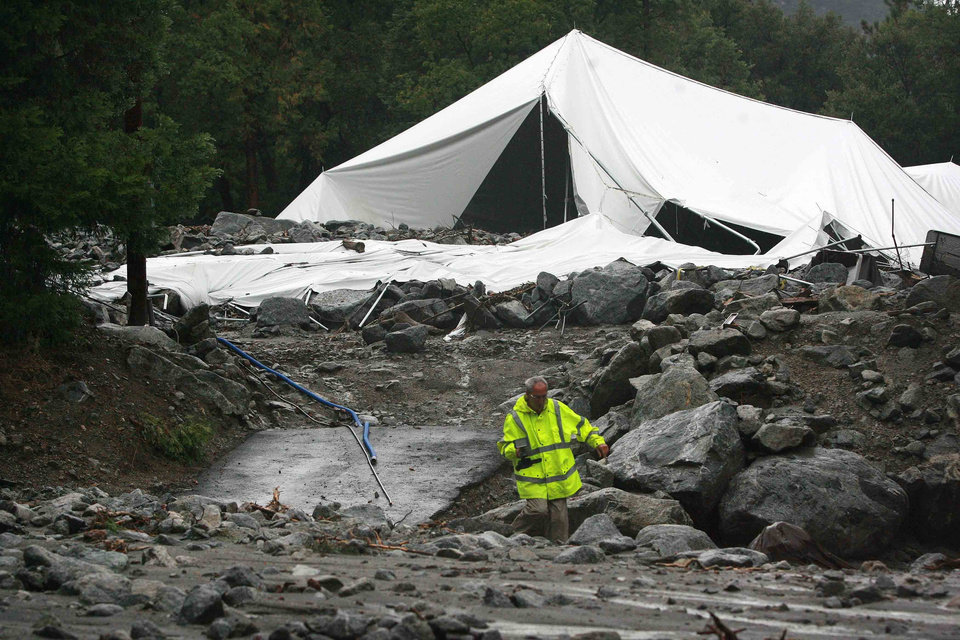 Photo - In this Sunday, Aug. 3, 2014 photo, videographer John Casper walks near a large tent at Forest Home Christian Conference Center in Forest Falls, Calif., that was partially destroyed following a rock and mudslide. Crews on Monday have cleared several feet of mud, rocks and debris that had blocked San Bernardino County roads, stranding some 2,500 people in the rural communities of Oak Glen and Forest Falls. (AP Photo/The Press-Enterprise, David Bauman)  MAGS OUT; MANDATORY CREDIT