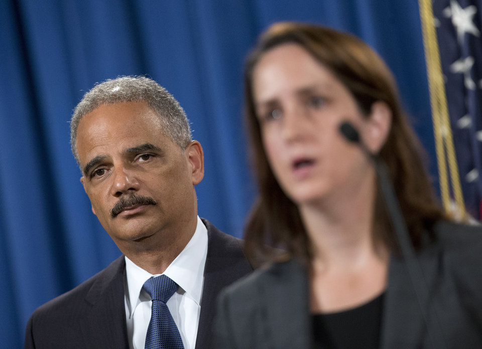 Photo - Attorney General Eric Holder listens at left during a news conference at the Justice Department in Washington, Thursday, Sept. 4, 2014, to announce the Justice Department's civil rights division will launch a broad civil rights investigation in the Ferguson, Mo., Police Department. At right is Acting Assistant Attorney General for Civil Rights Division Molly Moran. (AP Photo/Pablo Martinez Monsivais)