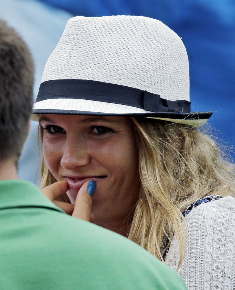Photo - Tennis player Caroline Wozniacki speaks with a spectator while watching Rory McIlroy, of Northern Ireland, during the first round of the Masters golf tournament Thursday, April 11, 2013, in Augusta, Ga. (AP Photo/David J. Phillip)