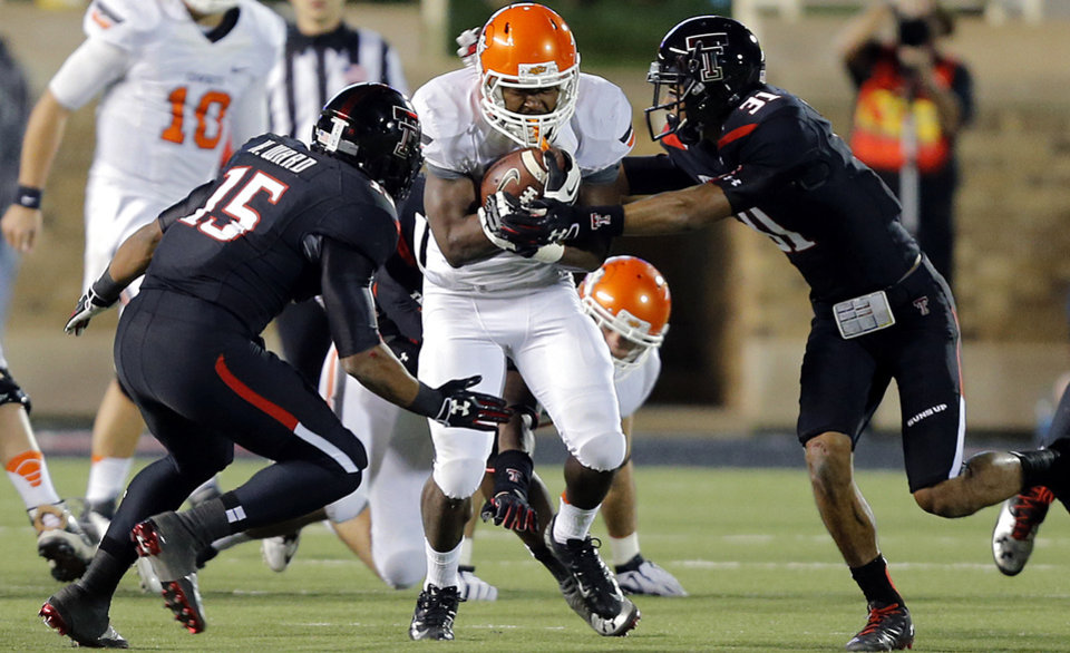 Oklahoma State 's Rennie Childs (23) runs through Texas Tech's Keenon Ward (15) and Justis Nelson (31) during the college football game between the Oklahoma State University Cowboys (OSU) and the Texas Tech University Red Raiders (TTU) at Jones AT&T Stadium in Lubbock, Tex. on Saturday, Nov. 2, 2013.  Photo by Chris Landsberger, The Oklahoman