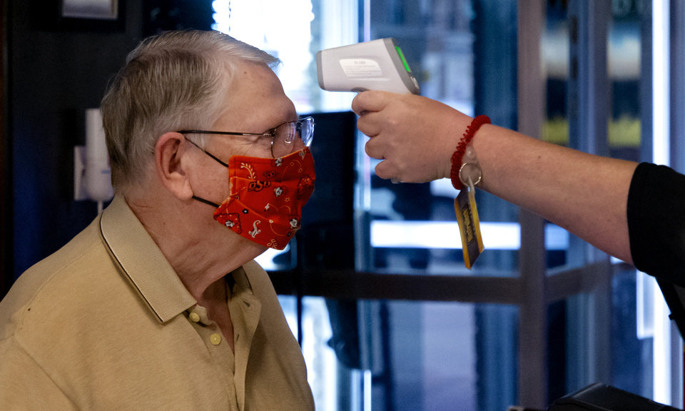 Photo - Owner Dick Stubbs has his temperature taken as he arrives for work at Cattlemen's Steakhouse in Oklahoma City, Okla. on Friday, May 1, 2020. All members of the staff sign in and have their temperature taken before starting their shift as the restaurant begins its gradual reopening on Friday after being closed due to the Coronavirus Pandemic.[Chris Landsberger/The Oklahoman]