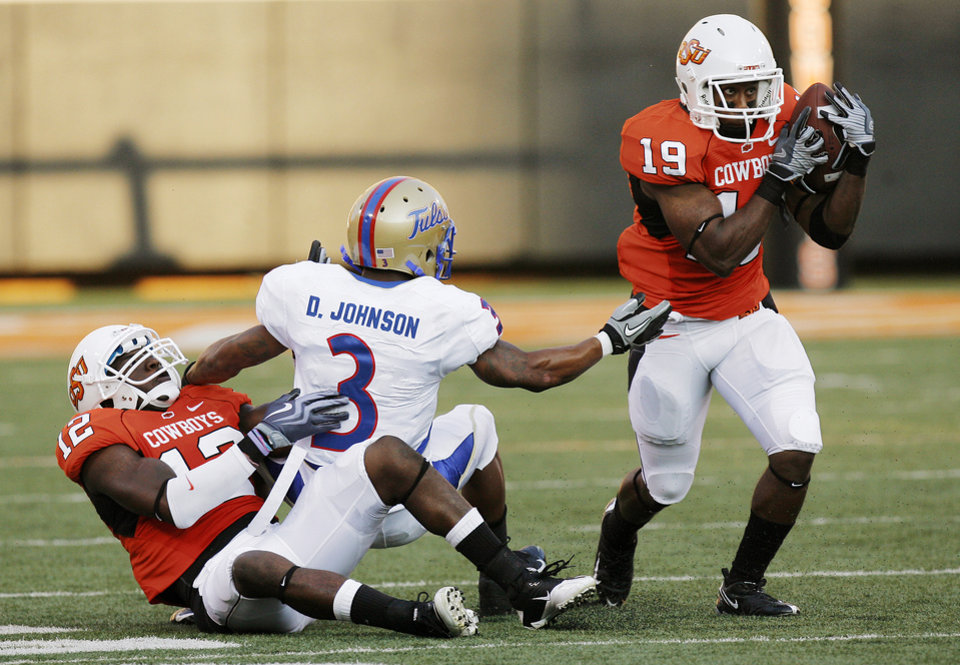 Photo - OSU's Brodrick Brown (19) intercepts a pass intended for TU's Damaris Johnson (3) as Johnny Thomas (12) of OSU defends in the first quarter during the college football game between the University of Tulsa (TU) and Oklahoma State University (OSU) at Boone Pickens Stadium in Stillwater, Oklahoma, Saturday, September 18, 2010. Photo by Nate Billings, The Oklahoman