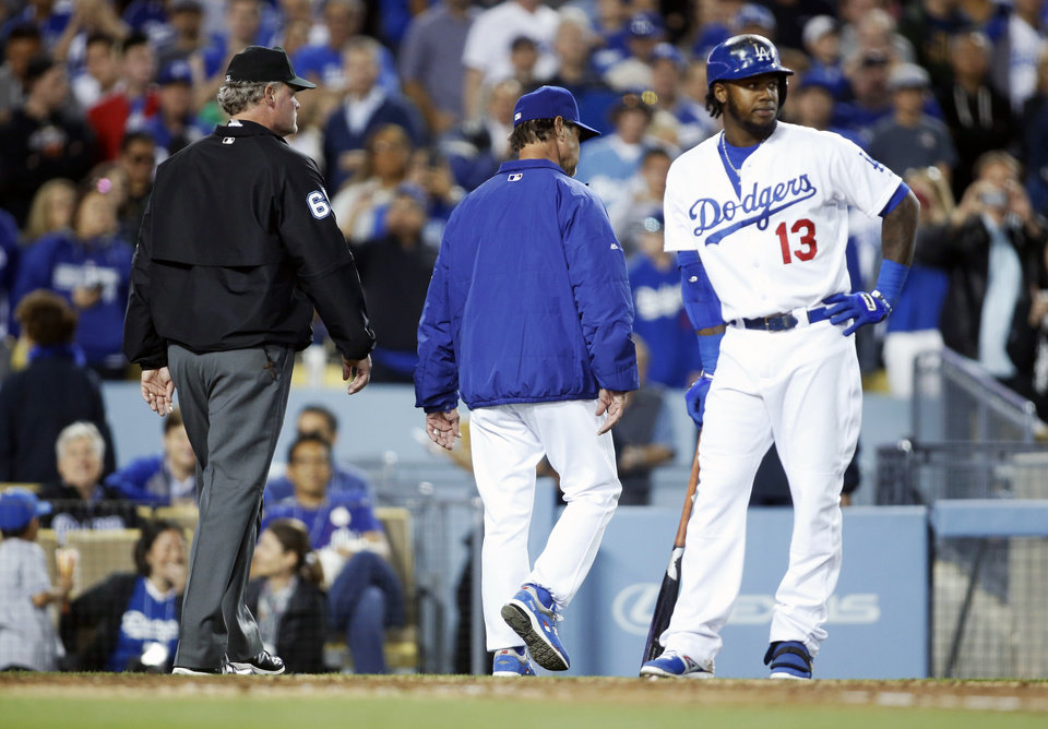 Photo - Los Angeles Dodgers' manager Don Mattingly leaves the field after being ejected as Hanley Ramirez, right, stands at the plate and umpire Ted Barrett, left, walks behind him against the San Francisco Giants during the seventh inning of a baseball game, Friday, May 9, 2014, in Los Angeles. (AP Photo/Danny Moloshok)