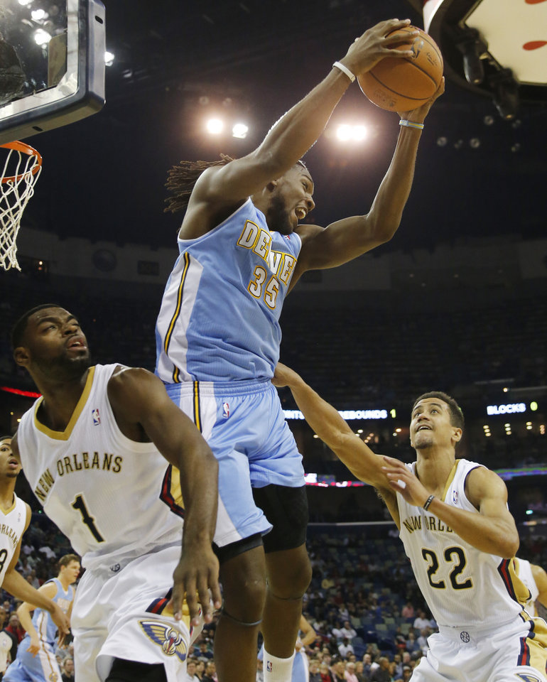 Photo - Denver Nuggets power forward Kenneth Faried (35) grabs a rebound in front of New Orleans Pelicans small forward Tyreke Evans (1) and point guard Brian Roberts (22) in the first half of an NBA basketball game in New Orleans, Sunday, March 9, 2014. (AP Photo/Bill Haber)