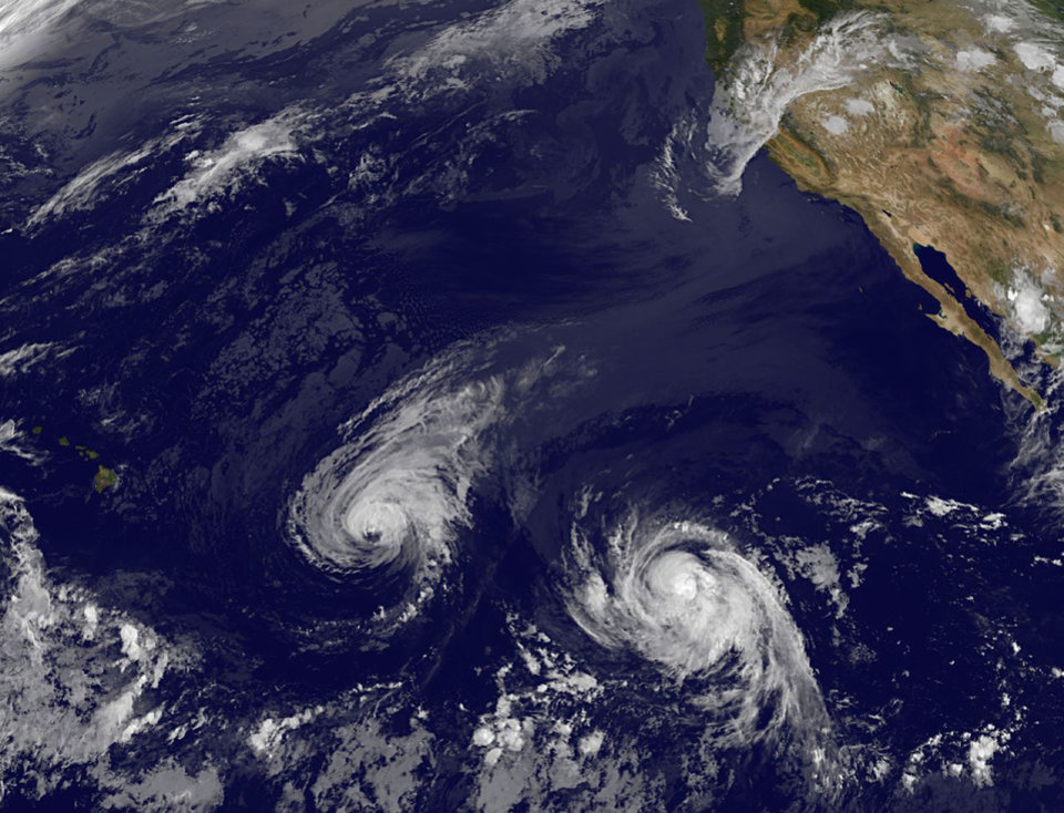 Photo - This image provided by NOAA taken Wednesday Aug. 6, 2014 shows Hurricane Iselle, center, and tropical storm Julio, right. Though it's not clear how damaging the storms could be, many in Hawaii aren't taking any chances as they wait for Hurricane Iselle to make landfall later this week and Tropical Storm Julio potentially hitting a few days later. (AP Photo/NOAA)
