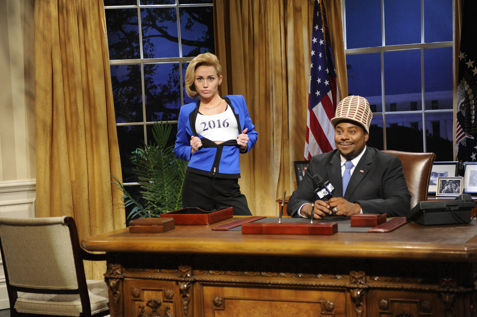 Photo - This Oct. 5, 2013 photo released by NBC shows guest host Miley Cyrus, left, and  Kenan Thompson in a scene from the late-night comedy series