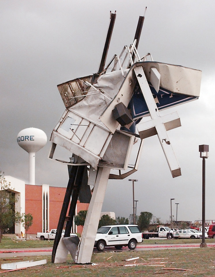 MAY 3, 1999 TORNADO: TORNADO DAMAGE: NE 27TH AND I-35 IN MOORE OKLA.  Cross on the south side of the First Baptist Church  twisted with the Moore water tower in the background.
