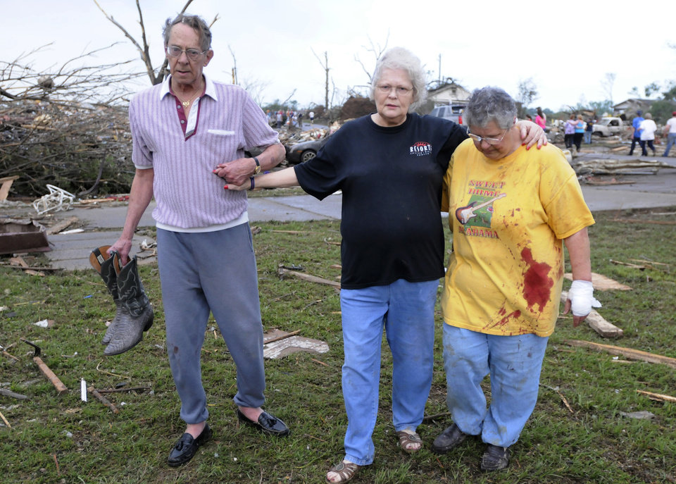 Photo - Clyde Lafon, from left, Alice Lafon and Liz Perry walk from the area where their houses stood, Wednesday, April 27, 2011, in Concord, Ala., after severe weather crossed the area. (AP Photo/Birmingham News, Jeff Roberts)