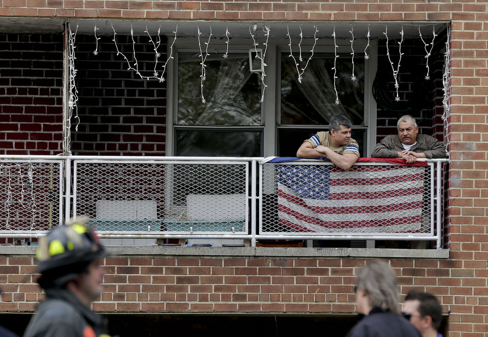 Photo - Residents of an apartment building at 60th Street and Broadway in Queens borough of New York,  watch as emergency crews evacuate passengers from a subway tunnel after a train derailed, Friday, May 2, 2014. The express F train was bound for Manhattan and Brooklyn when it derailed at 10:40 a.m. Dozens of firefighters and paramedics with stretchers converged on Broadway and 60th Street, where passengers calmly left the tunnel through the sidewalk opening. A few were treated on stretchers. (AP Photo/Julie Jacobson)