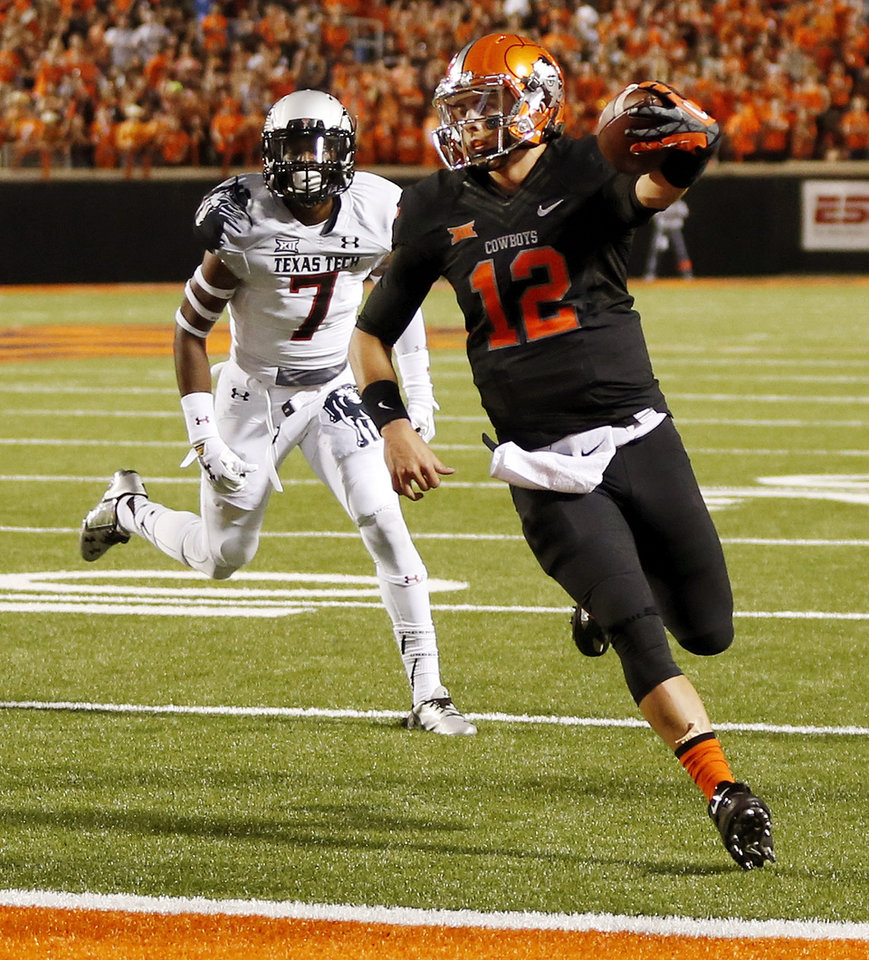 Photo - Oklahoma State's Daxx Garman (12) carries the ball for a touchdown in front of Texas Tech's Josh Keys (7) in the fourth quarter during a college football game between the Oklahoma State Cowboys (OSU) and the Texas Tech Red Raiders at Boone Pickens Stadium in Stillwater, Okla., Thursday, Sept. 25, 2014. OSU won, 45-35. Photo by Nate Billings, The Oklahoman